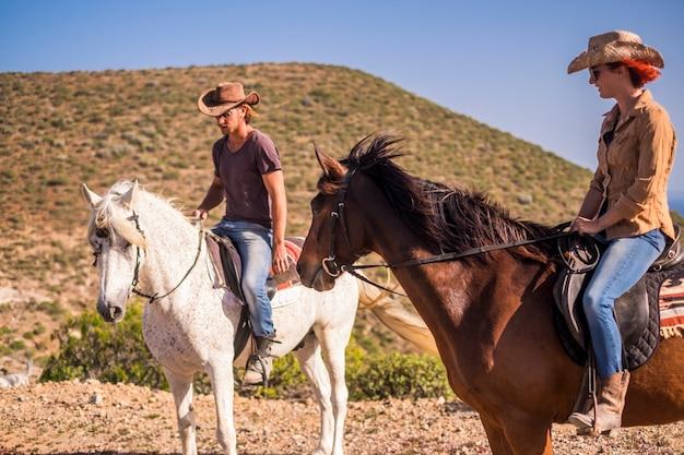 Un couple de cavaliers homme et femme avec des chevaux bruns et blancs va profiter de l'activité de loisirs de plein air en excursion parcourant les montagnes. cowboy moderne et aucune technologie