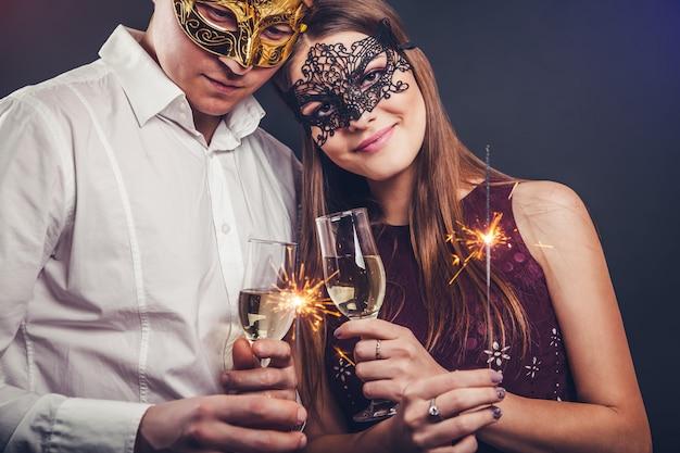 Couple célébrant le nouvel an buvant du champagne et allumant des feux de bengale lors d'une soirée masquerade