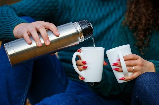 Couple en chandails boit du thé dans la forêt d'automne