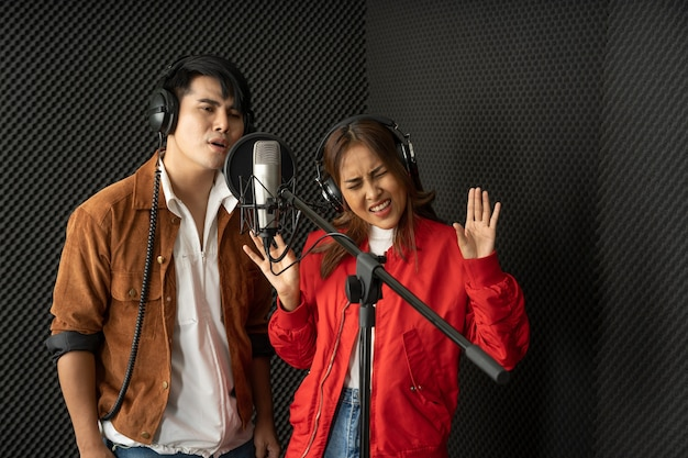 Couple de chanteurs asiatiques dans un studio d'enregistrement utilisant un microphone de studio avec passion dans un studio d'enregistrement musical