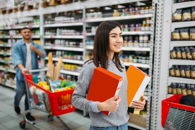 Couple avec chariot au supermarché, département des boissons, shopping familial. clients achetant des boissons en magasin, acheteurs sur le marché