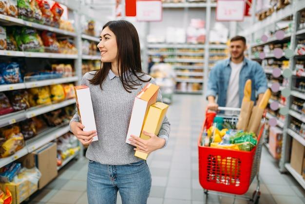 Couple avec chariot au supermarché, département des boissons