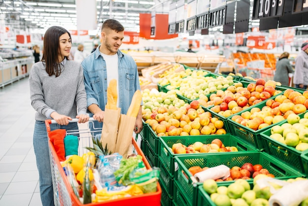 Couple avec chariot au supermarché, rayon fruits, shopping familial. clients en boutique, acheteurs sur le marché