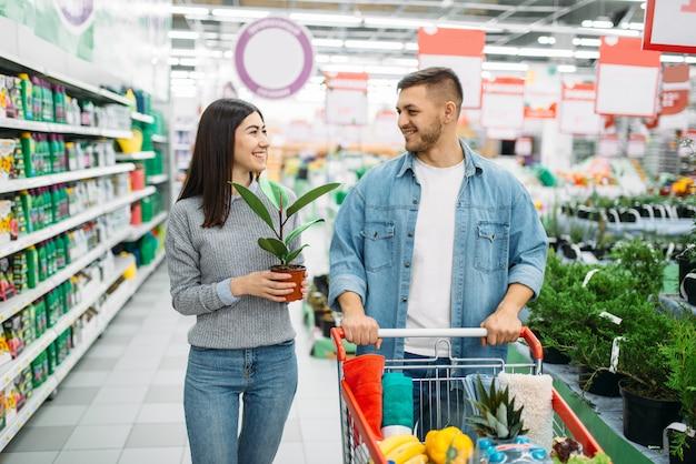 Couple avec chariot plein de produits achetant des fleurs à la maison dans un supermarché, shopping familial. clients en boutique, acheteurs sur le marché