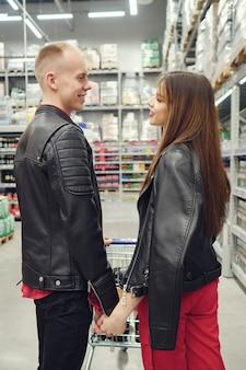Couple avec chariot se regarde dans le marché, vue arrière