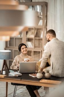Couple charmant à la recherche. homme barbu en cardigan gris assis sur la surface de la table et parler à sa charmante femme