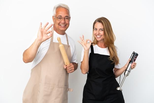 Couple de chefs d'âge moyen isolé sur fond blanc montrant un signe ok avec les doigts