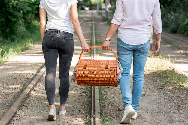 Couple sur un chemin de fer portant un panier de pique-nique