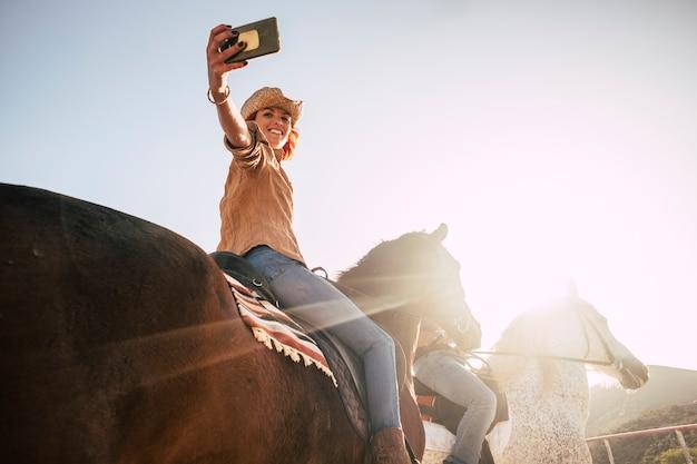 Un couple à cheval prend un selfie avec un smartphone à technologie moderne