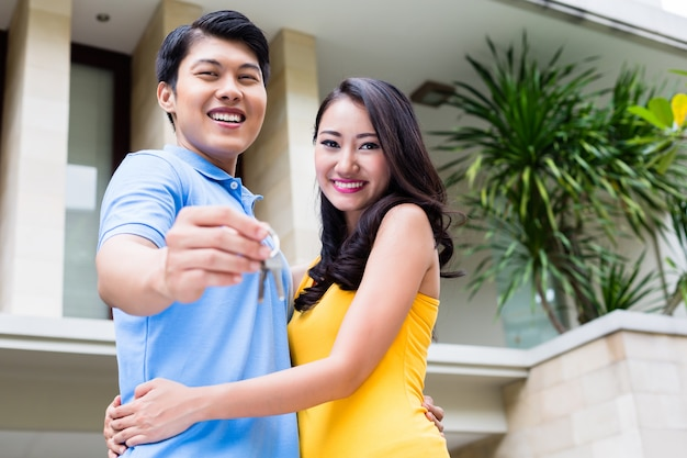 Couple chinois montrant les clés de leur nouvelle maison