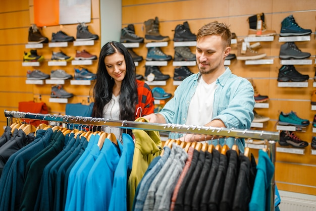 Couple choisissant combinaison de cyclisme, shopping dans un magasin de sport.