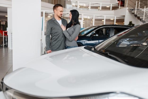 Couple choisissant une nouvelle voiture dans la salle d'exposition