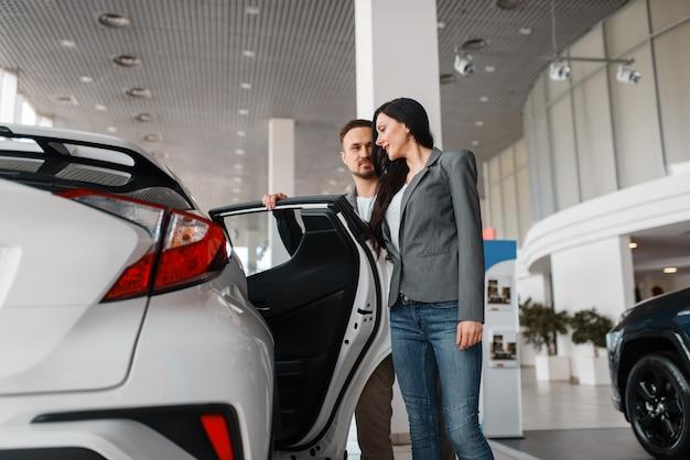 Couple choisissant une nouvelle voiture dans la salle d'exposition.