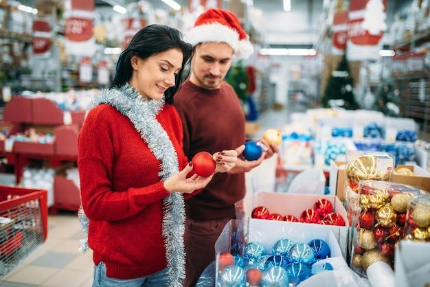 Couple choisit des boules de sapin de noël au supermarché