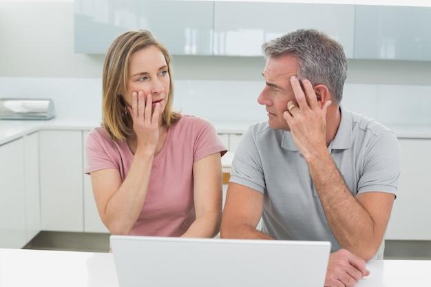 Couple choqué à l'aide d'un ordinateur portable dans la cuisine