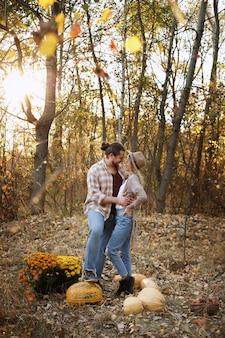 Couple avec des citrouilles à l'automne lors d'une promenade
