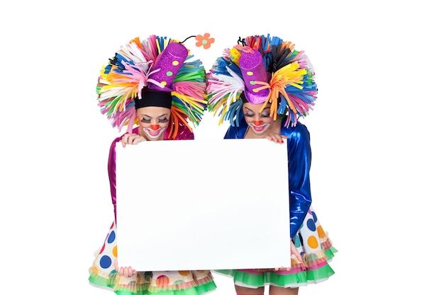Couple de clowns drôles avec une affiche vide isolé sur fond blanc