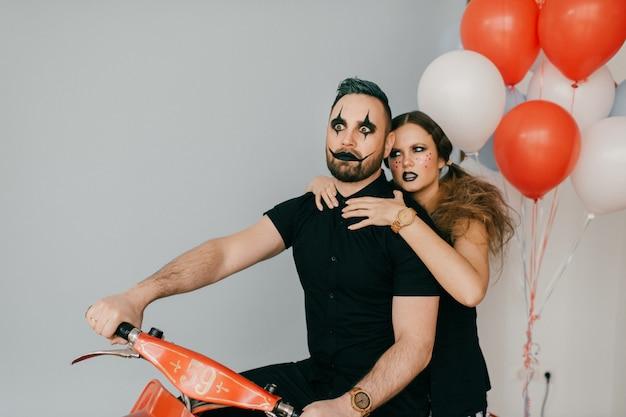Un couple de clowns posant sur moto