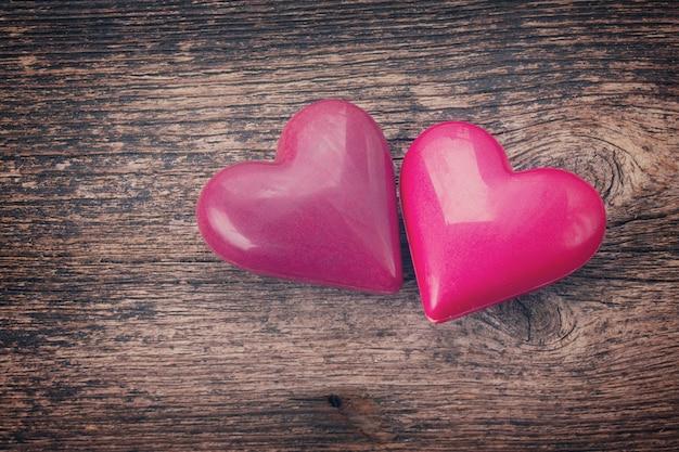 Couple de coeurs roses portant ensemble sur fond de bois, aux tons rétro