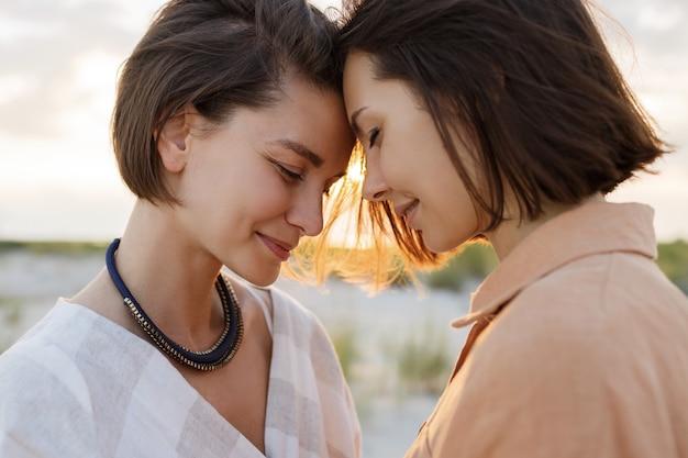 Couple avec une coiffure courte en vêtements d'été en lin posant sur la plage