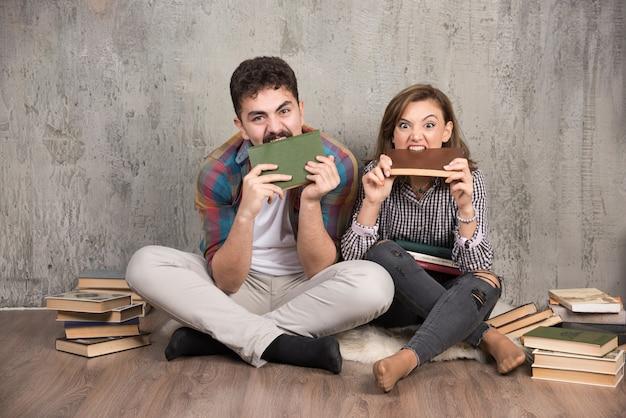 Couple en colère mordant des livres