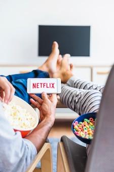 Couple avec des collations en regardant la série netflix dans le salon