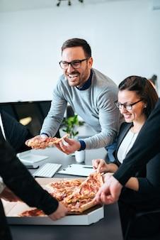 Couple de collègues en train de déjeuner, manger une pizza.