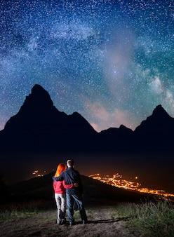 Couple sur la colline sous les étoiles brillantes