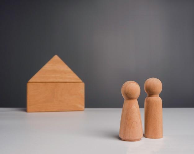 Un couple commence une vie avec le concept d'investissement immobilier. le couple humain en bois debout devant une miniature de maison en bois sur fond gris, style minimal.