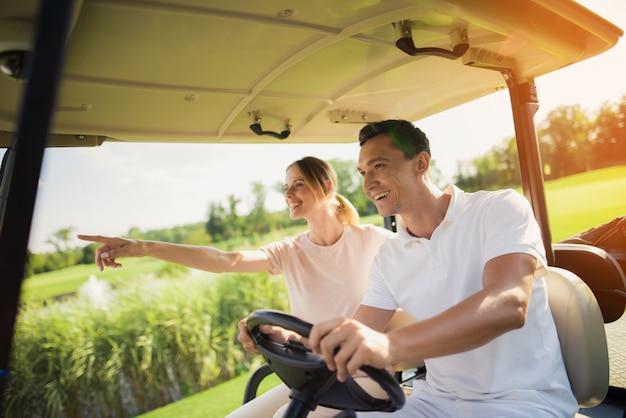 Un couple conduit une voiture de golf profite du paysage.