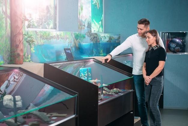 Le couple considère l'exposition au musée.