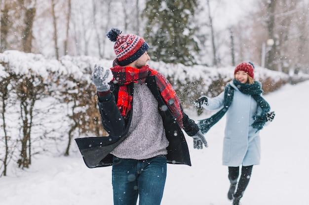 Couple de contenu jouant des boules de neige dans le parc