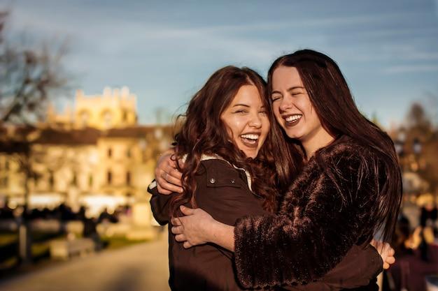 Couple de copines s'embrassant avec amour dans un parc en plein air symbole de l'amour