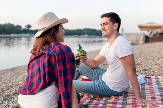 Couple sur le côté grillage sur une couverture de pique-nique
