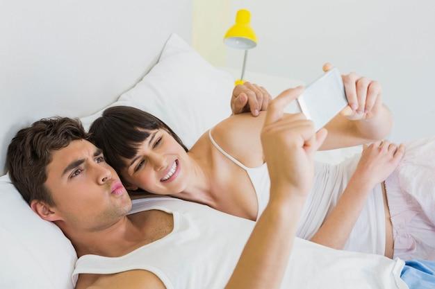 Couple, coucher lit, et, regarder, téléphone portable, dans chambre à coucher