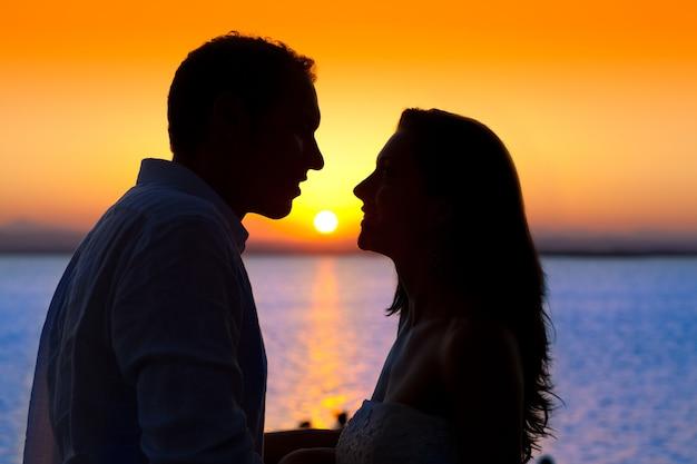 Couple coucher de soleil profil rétro-éclairage en mer orange