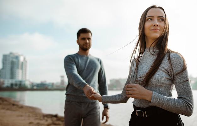 Couple coup moyen, main dans la main à la plage