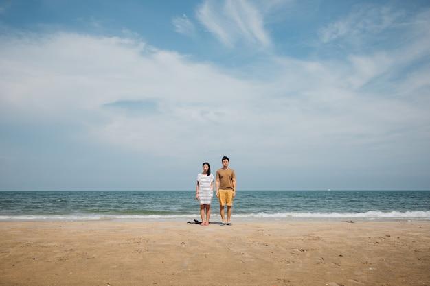 Couple couple debout pour prendre une photo minimale de la plage.