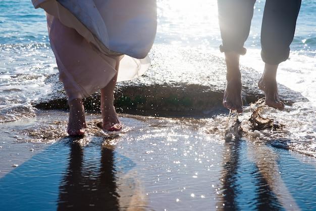 Couple de couple hétérosexuel s'amuser éclaboussant les vagues sur la plage.