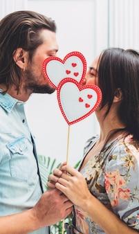 Couple couvrant les visages avec des coeurs de papier sur un bâton