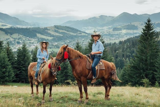 Couple de cow-boy à cheval dans les montagnes