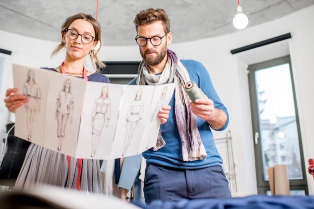 Couple de créateurs de mode travaillant avec des croquis de vêtements au studio