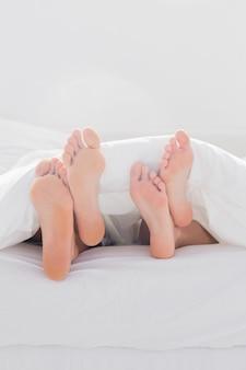 Couple, croisement, pieds, couette, lit