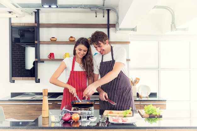 Couple cuisine dans leur cuisine.
