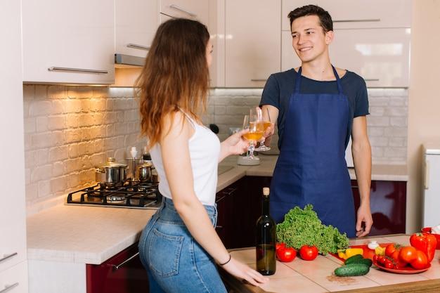 Couple cuisine ensemble et dégustation de vin.