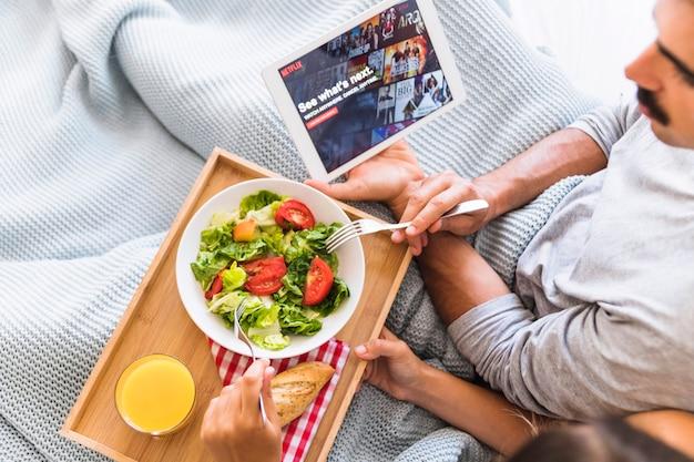 Couple de cultures avec salade regarder des émissions de télévision