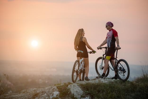Couple de cyclistes avec des vélos de montagne debout sur un rocher, appréciant le paysage de la soirée