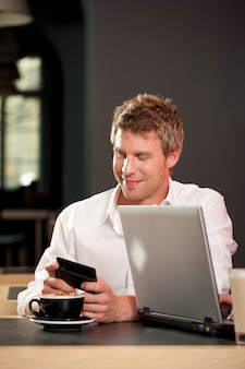 Couple dans le café avec ordinateur portable et mobile