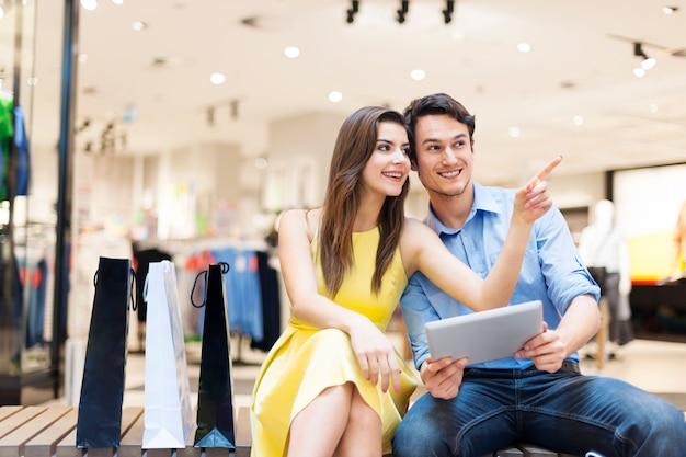 Couple dans un centre commercial à l'aide de tablette numérique