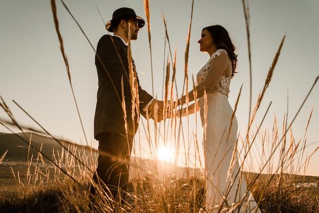 Couple dans un champ au coucher du soleil parmi les plantes sèches